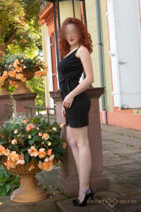 Mädchen steht neben einem Blumentopf