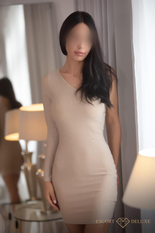 Escort Model trägt ein helles Kleid
