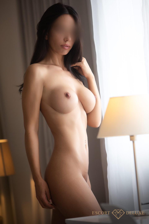 Chloe steht nackt vor dem Fenster