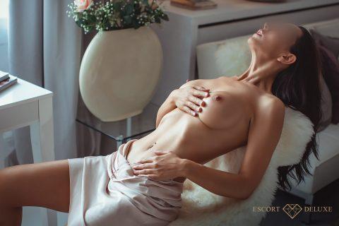Escort Dame streichelt ihre Brust