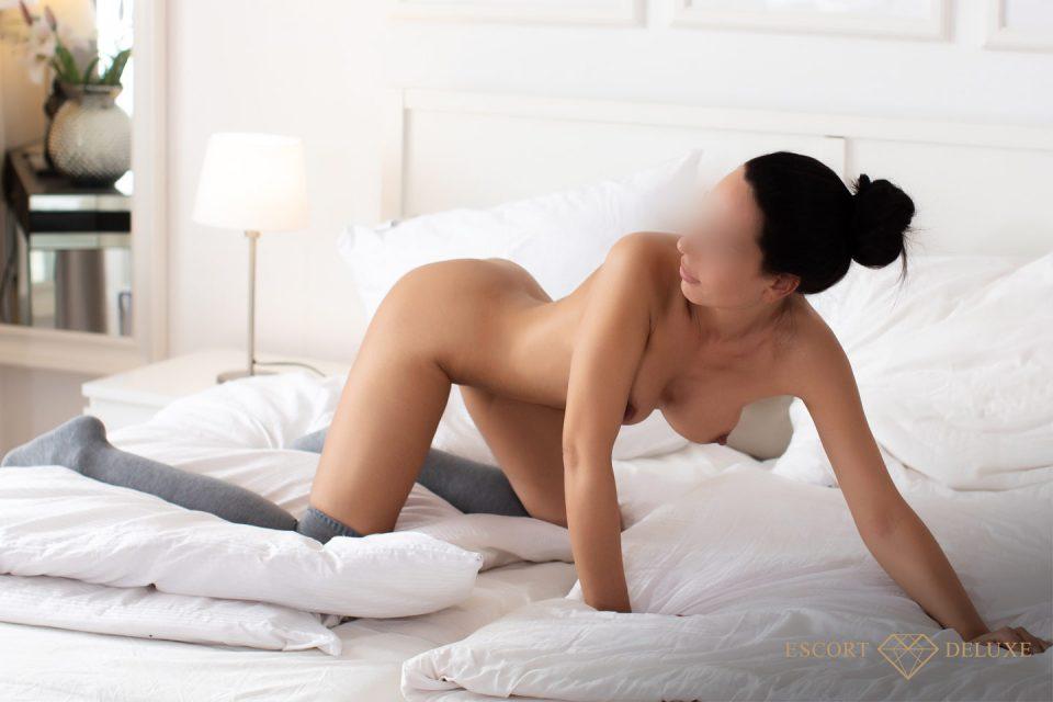 Escort Dame kniet auf dem Bett