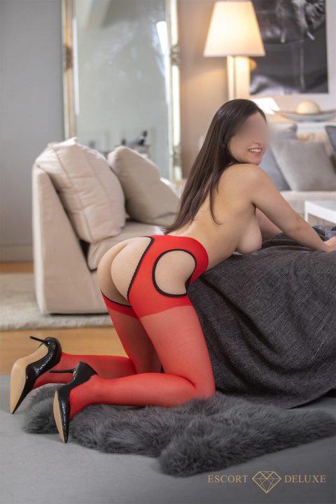 Escort Dame trägt rote Strümpfe