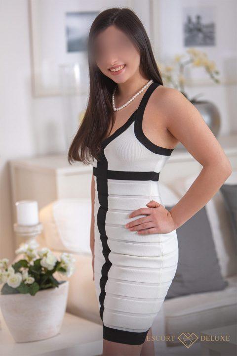 Escort Dame trägt ein weißes Kleid