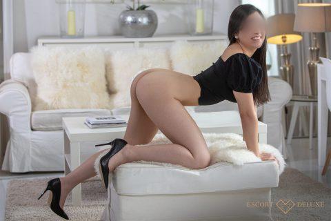 Model kniet auf dem Sessel