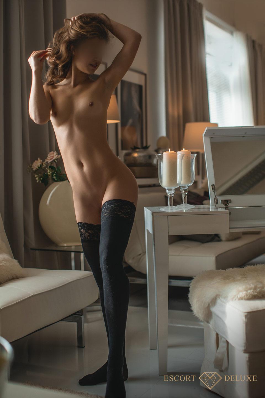 Escort Dame trägt halterlose Strümpfe