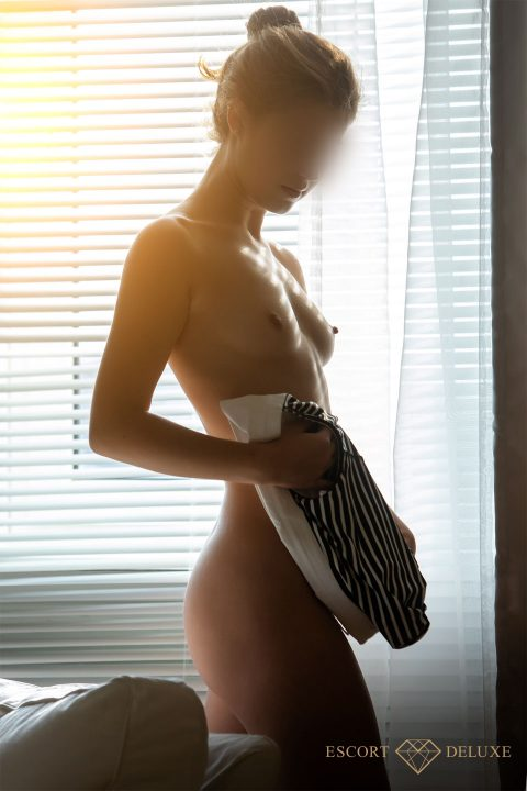 Escort lady stands in front of the window