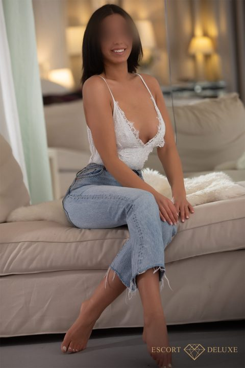 Escort Model sitzt auf der Couch