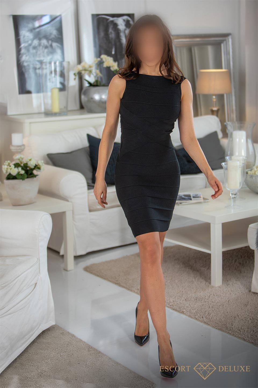 Escort Dame trägt ein schwarzes Kleid