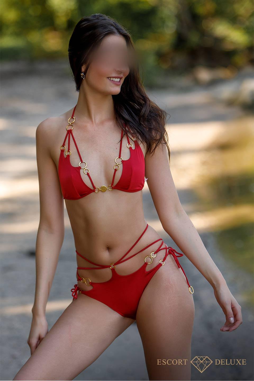 Escort Dame trägt ein roten Bikini