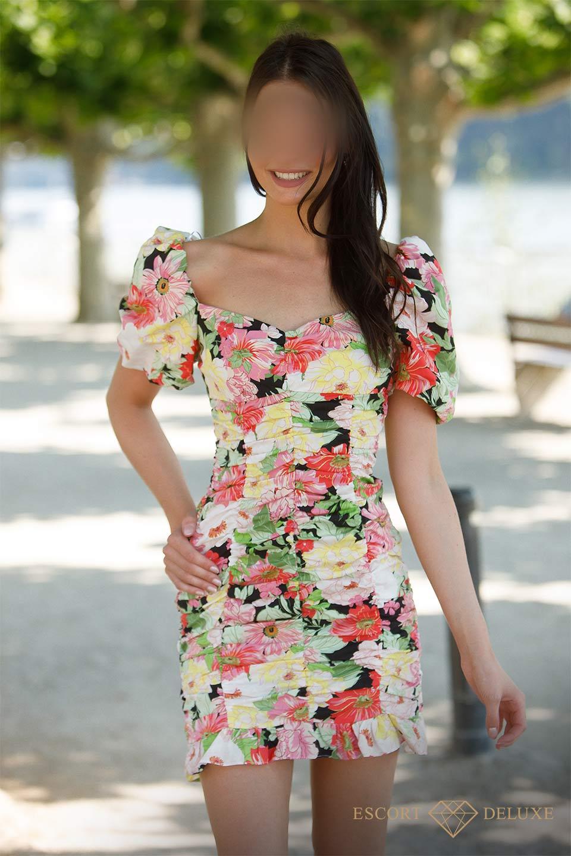 Escort Dame trägt ein Kleid mit Blumen