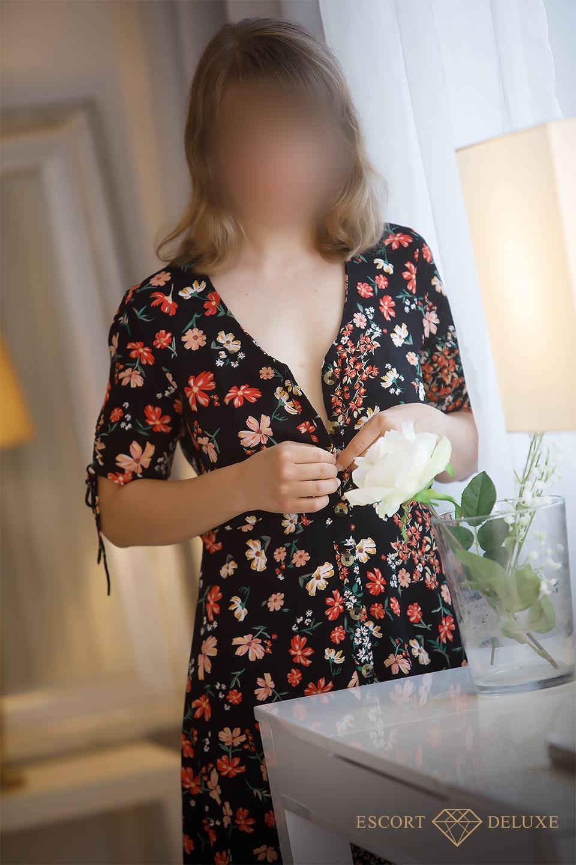 Escort Dame trägt ein Blumenkleid