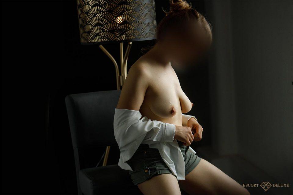 Escort Dame zieht ihre Bluse aus