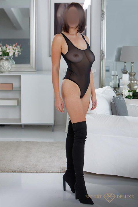 Dame trägt einen transparenten Body mit Overknees