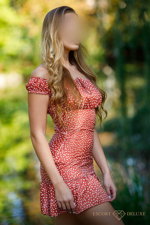 Model trägt ein rotes Kleid mit weißen Punkten