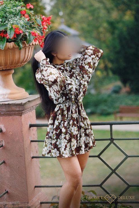 Escort Model trägt ein Blumenkleid