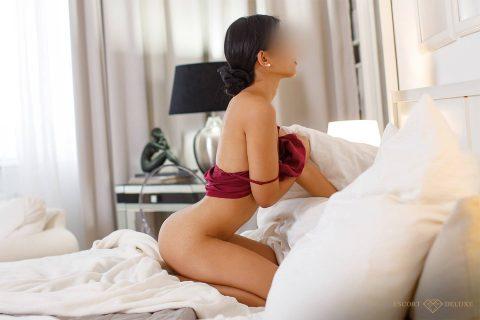 Escort Model kniet im Bett