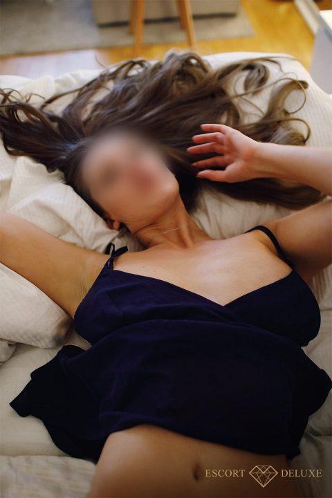Escort Model liegt auf dem Bett