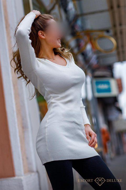 Sophie lächelt und trägt ein weißes Oberteil